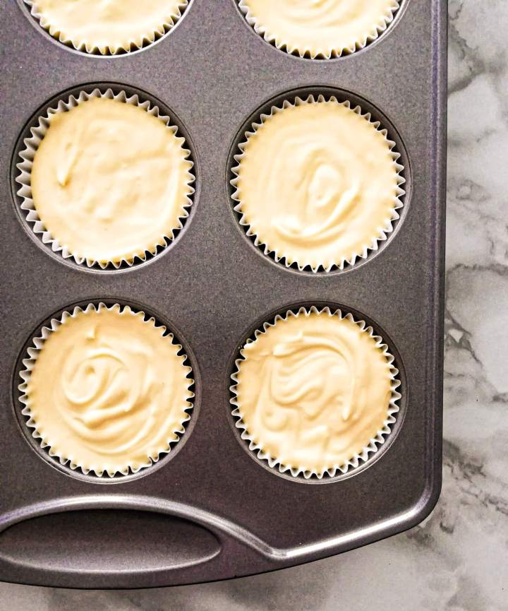 mini cheesecakes muffin tin filled with cheescake batter