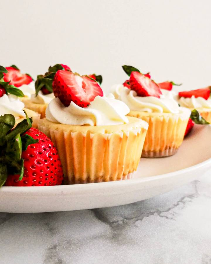 mini cheesecakes topped with whipped cream and strawberries 3