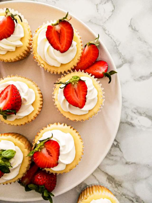 mini cheesecakes topped with whipped cream and strawberries overhead
