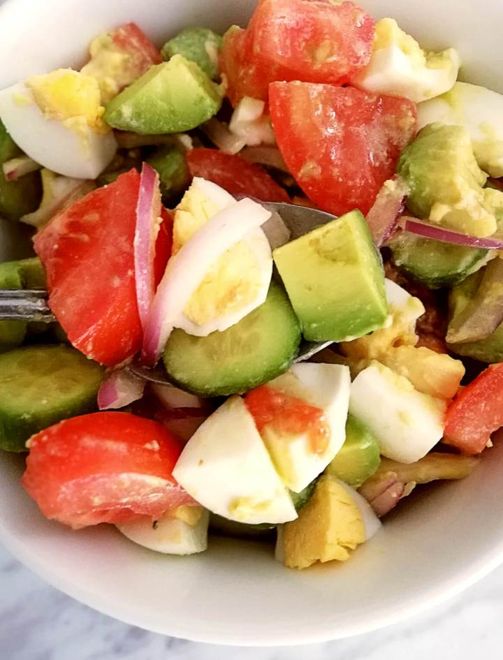 egg and avocado salad on spoon in bowl