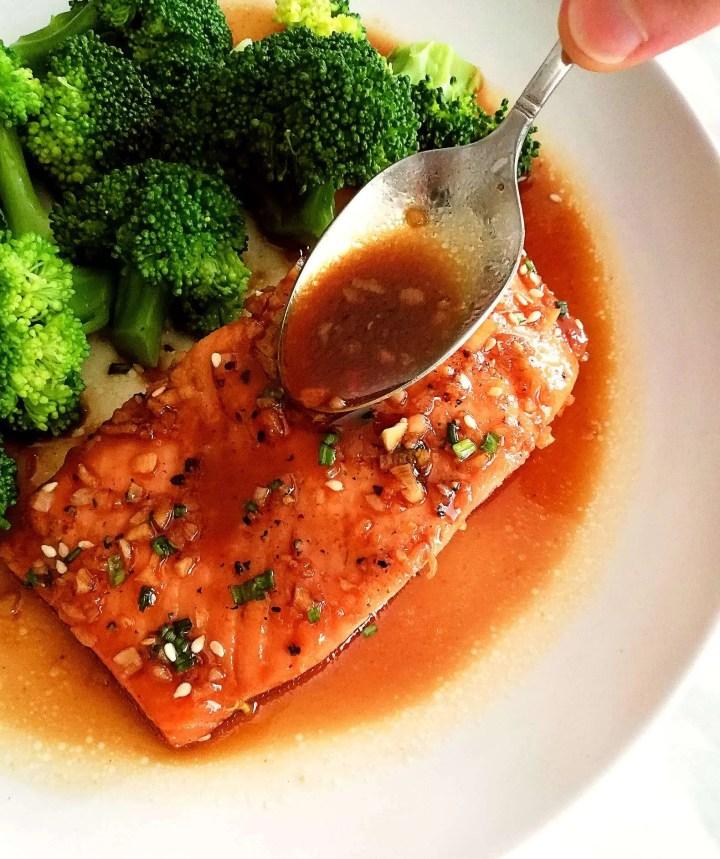 honey garlic salmon in plate spooning on sauce