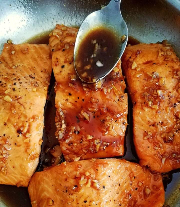 honey garlic salmon in skillet spooning sauce on top