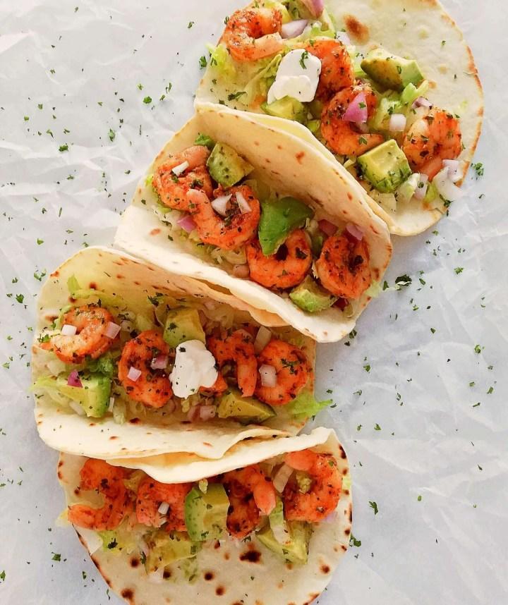 4 shrimp tacos lined up overhead