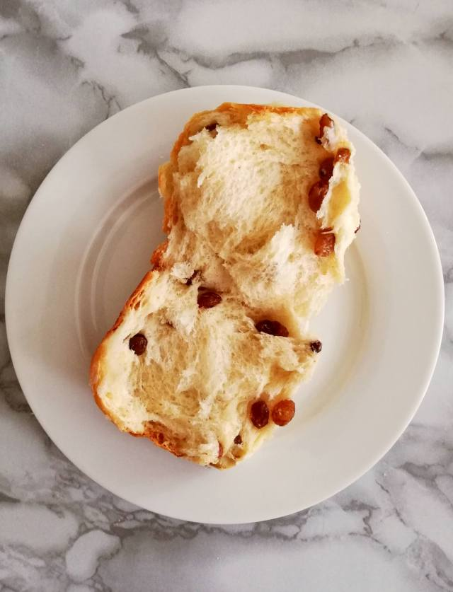 Easter hot cross buns split in half on plate overhead