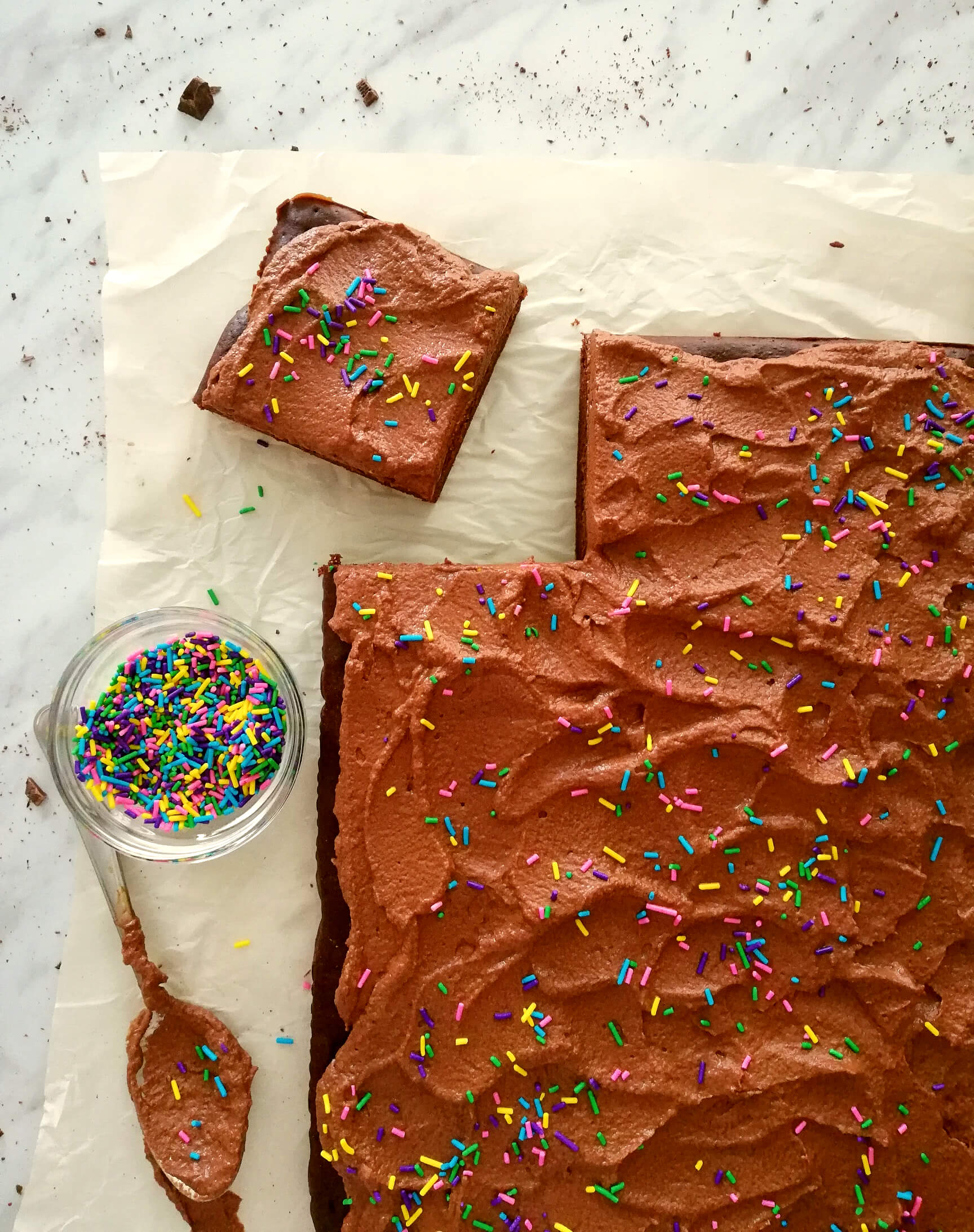 chocolate sheet cake with whipped ganahce frosting sliced overhead