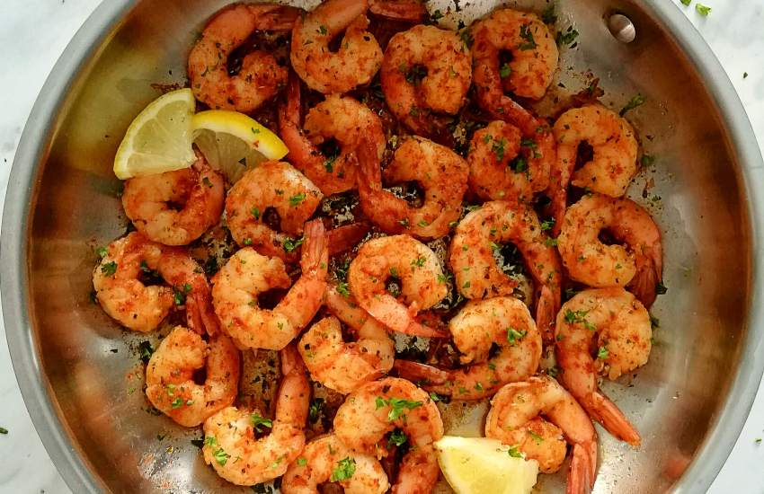 spicy shrimp in skillet topped with parsley and lemon slices