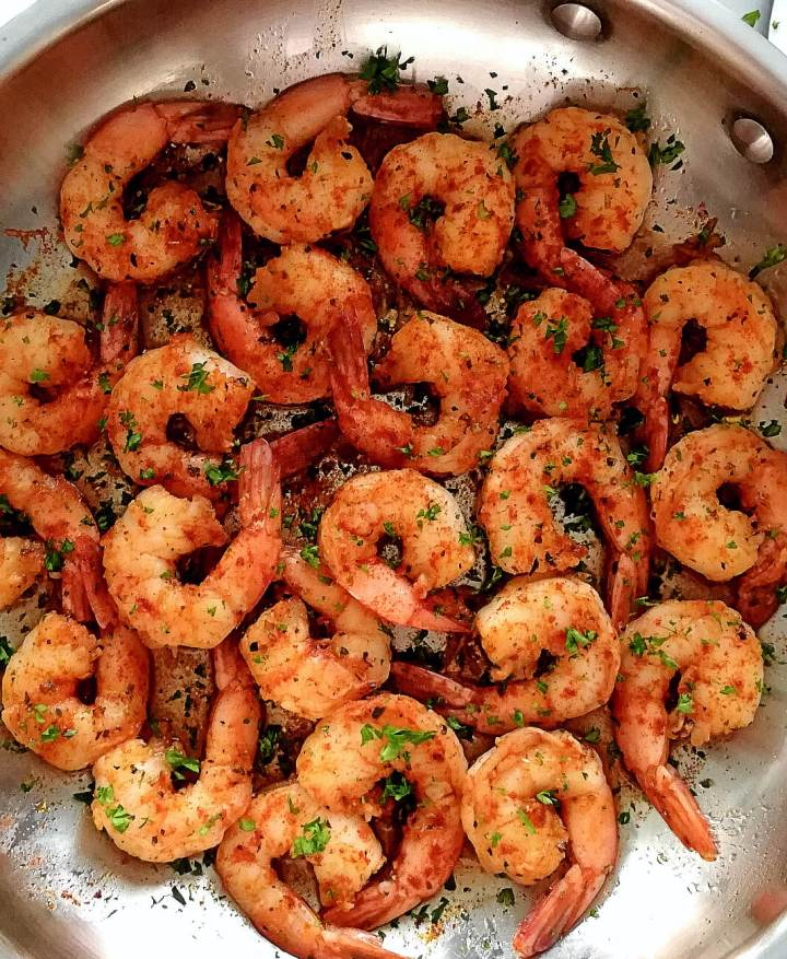 spicy shrimp in skillet topped with parsley