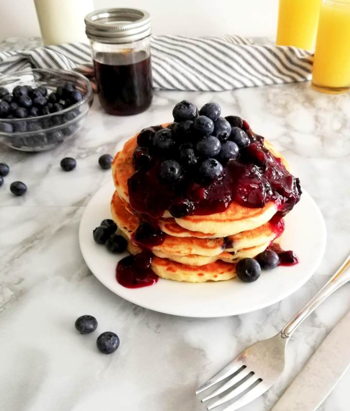 blueberry pancakes stacked and topped with blueberry sauce three quarter view