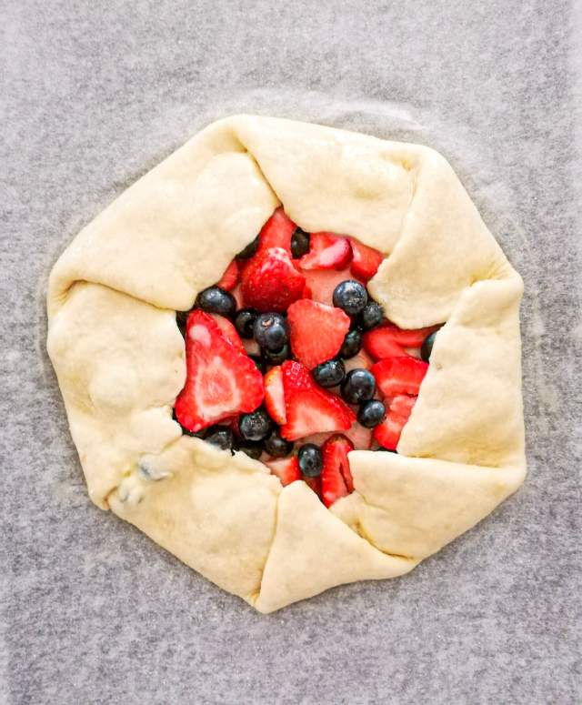 mixed berry galette filled and shaped on baking sheet overhead view