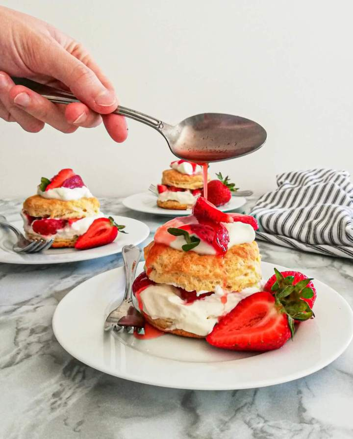 pouring strawberry juice over strawberry shortcake in plate (1)