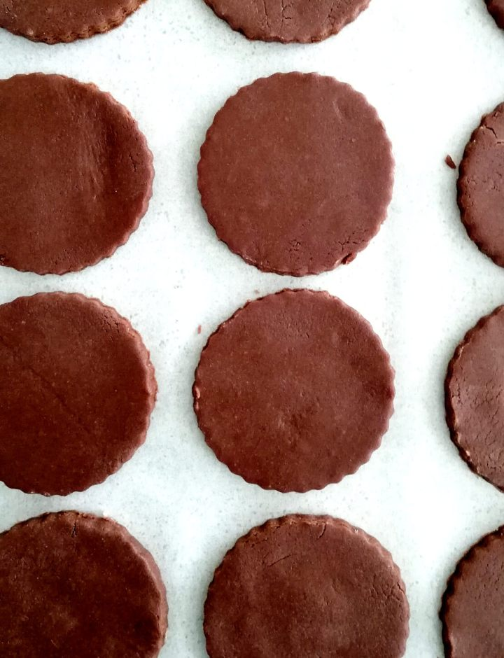 double chocolate sandwich cookies cut out and on baking sheet