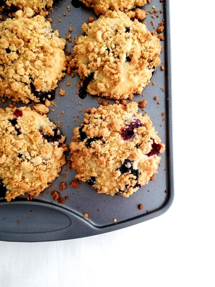 blueberry muffins in tin topped with streusel baked overhead image