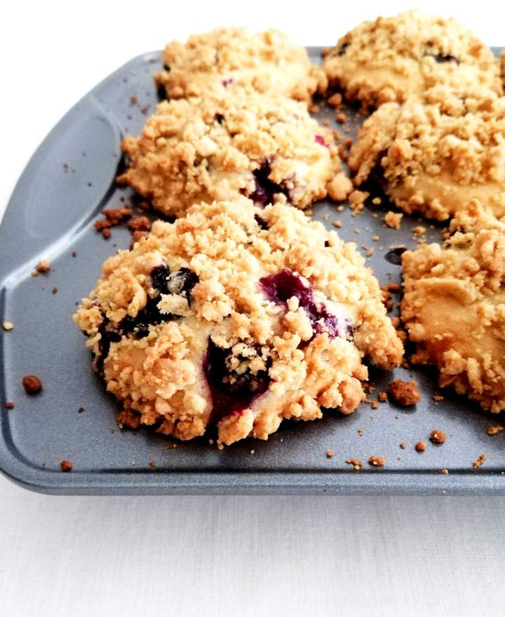 blueberry muffins in tin topped with streusel baked