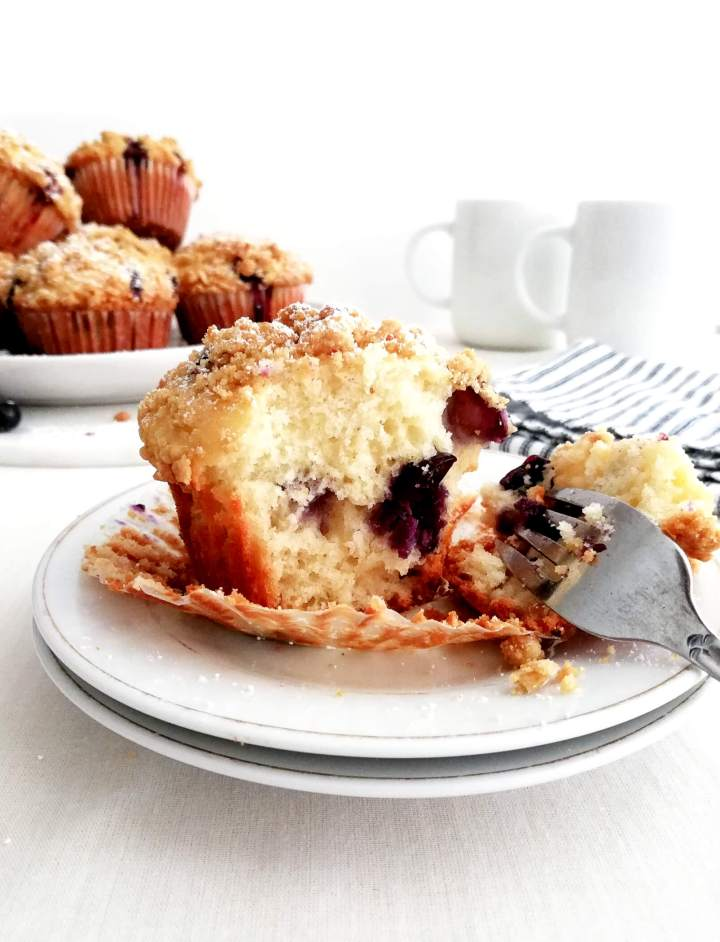 blueberry muffins with streusel topping muffin in plate cut open with fork