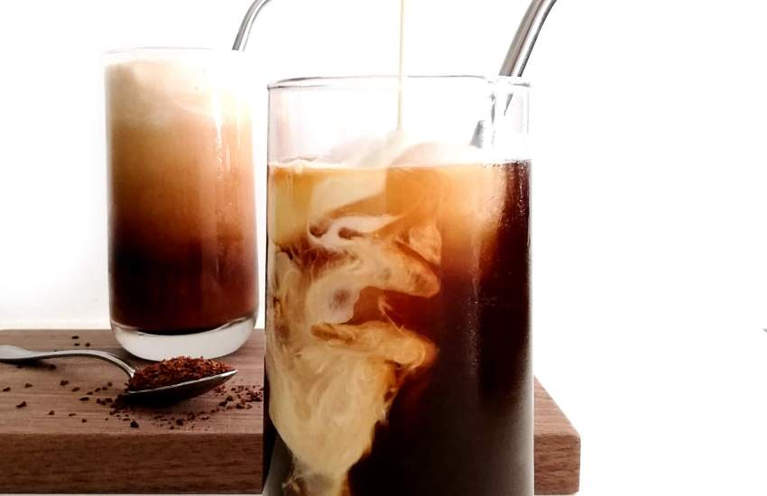 iced coffee in glasses pouring whipped cream into cup