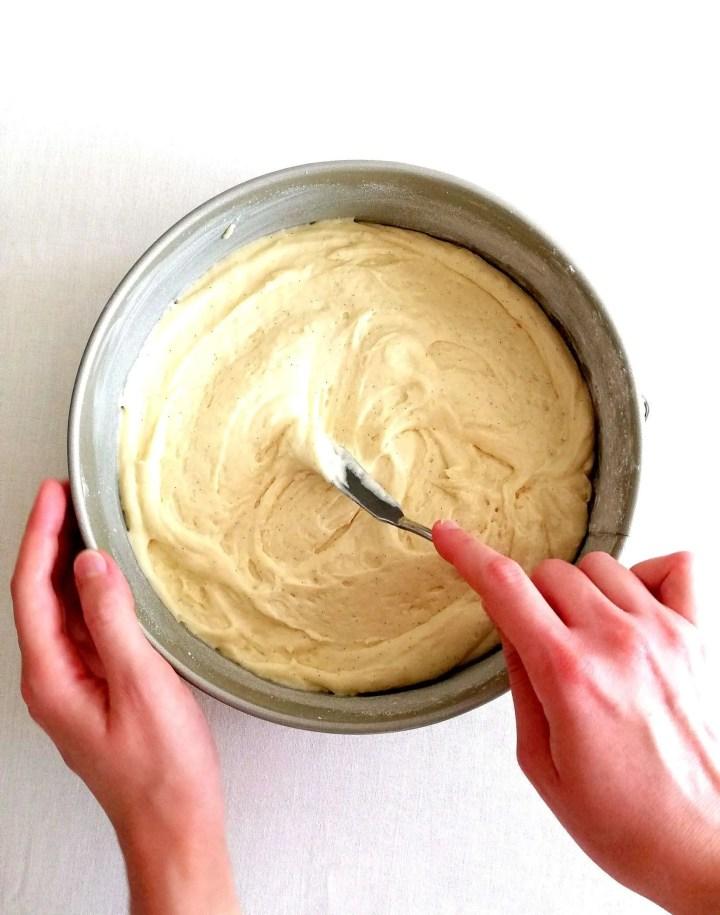 coconut jam cake spreading batter into cake pan