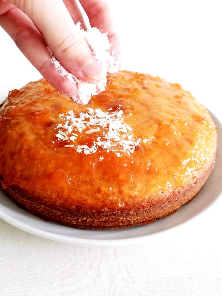 coconut jam cake topped with jam and sprinkling coconut on top