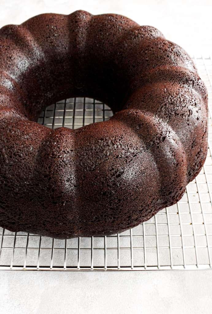 baked chocolate bundt cake on wire rack three quarter view