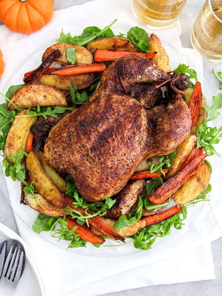 fall spice roasted chicken in plate over bed of veggies