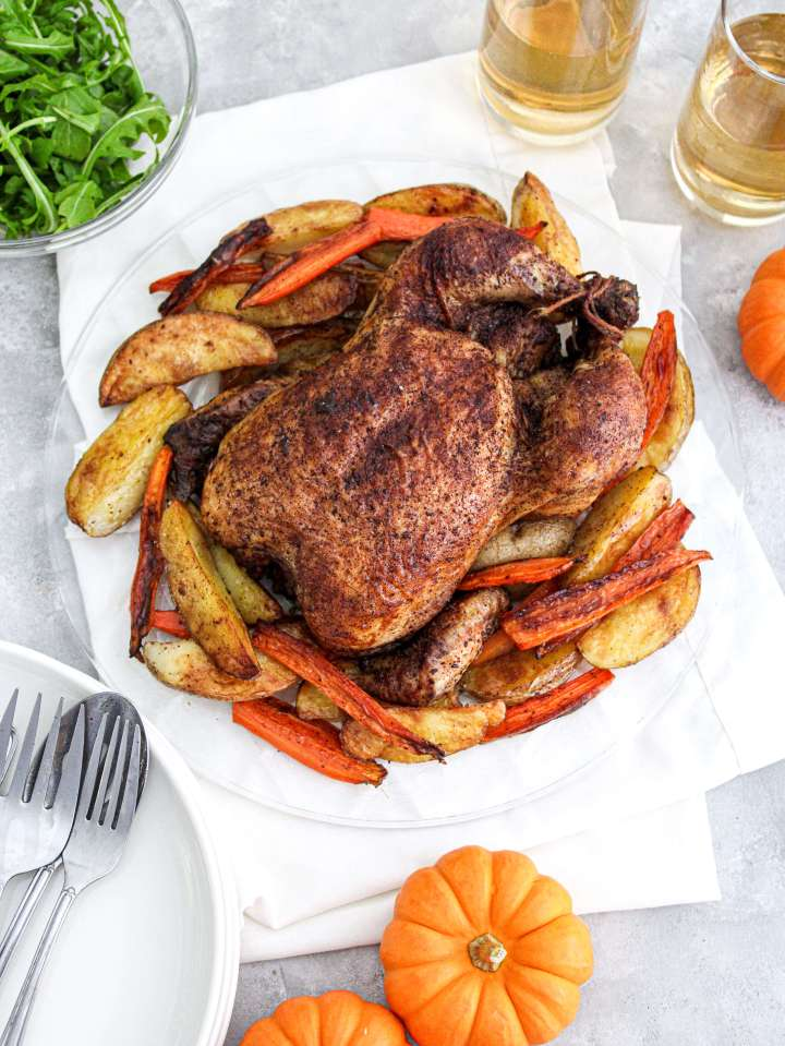fall spice roasted chicken in plate over roasted veggies