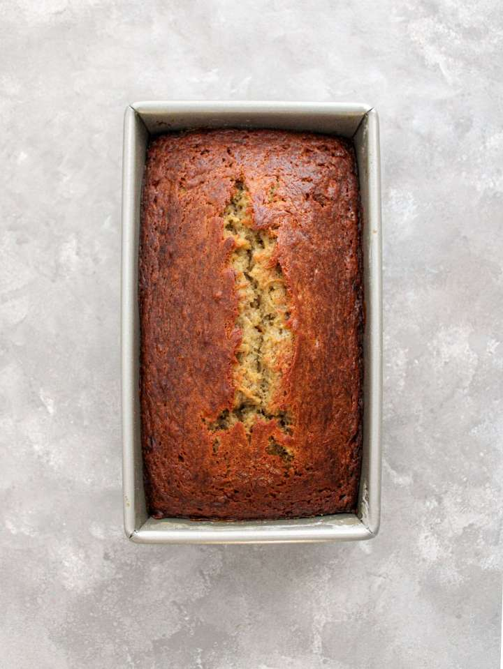 baked banana bread in loaf pan overhead image