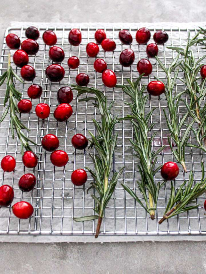 sugared cranberries and rosemary tossed in syrup and on wire rack to dry