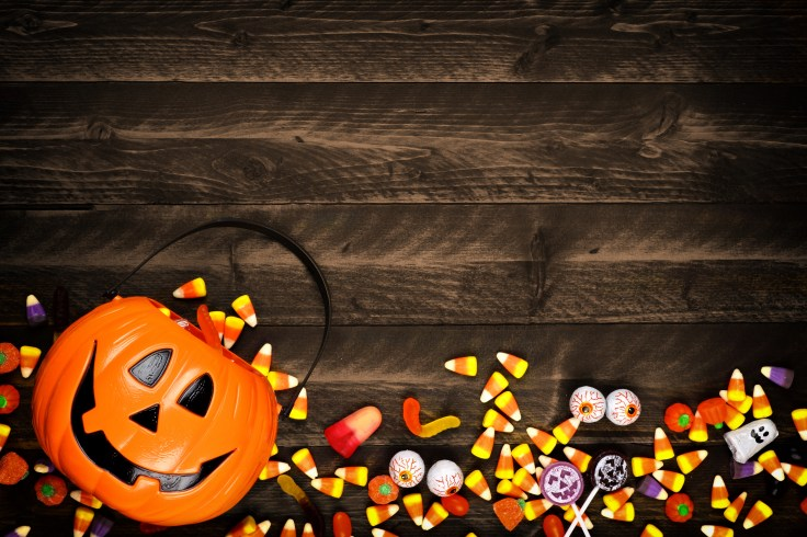 Halloween Jack o Lantern pail with bottom border of spilling candy over dark wood