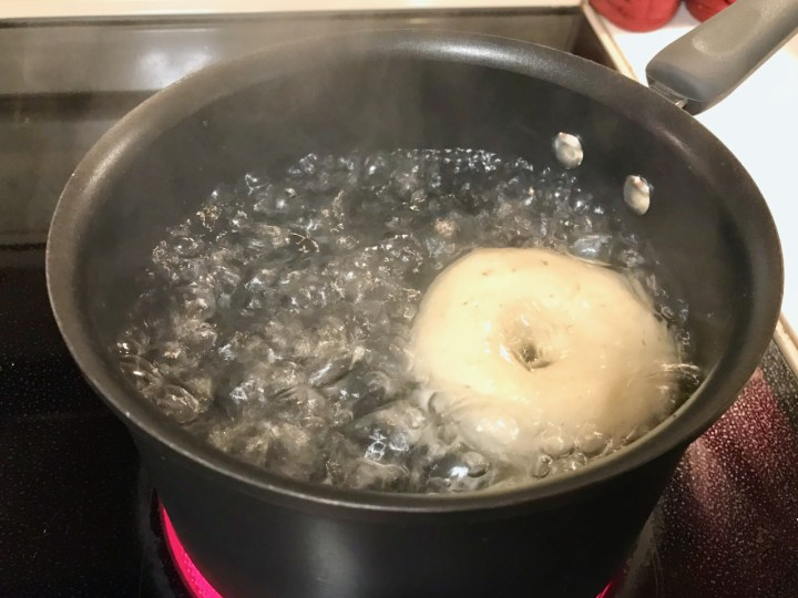 A single bagel boiling in a pot of water.