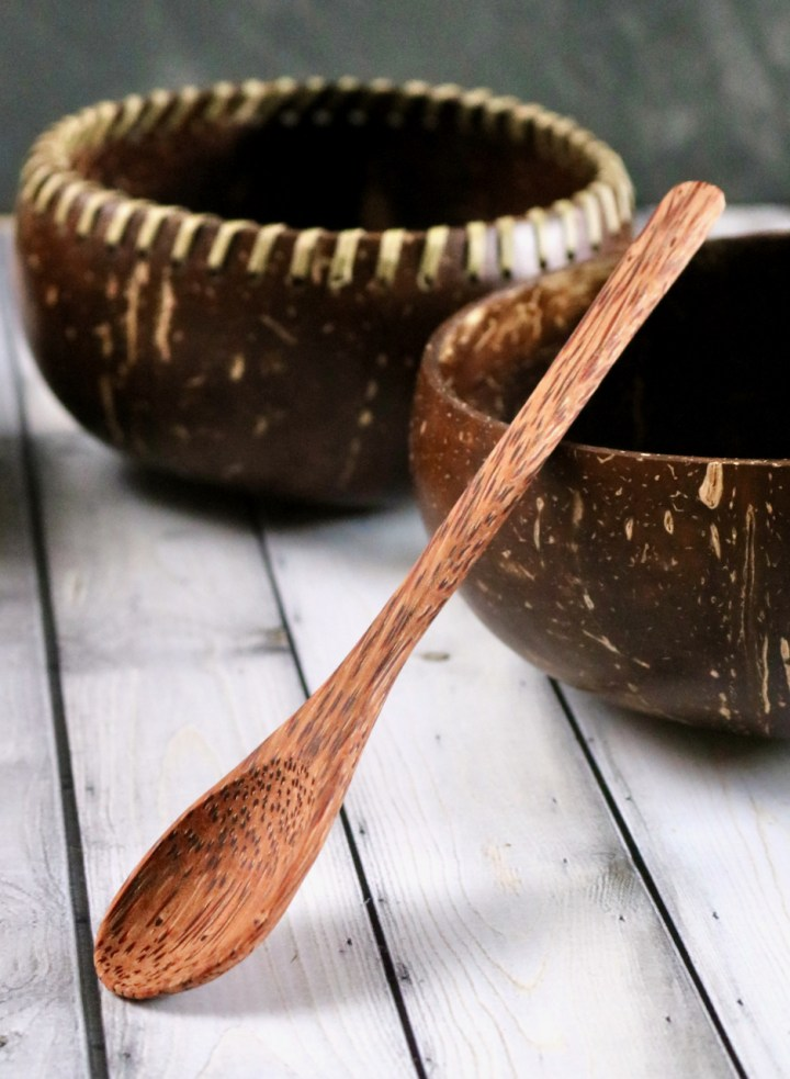 A spoon made from coconut timber propped up against a coconut shell repurposed as a bowl.