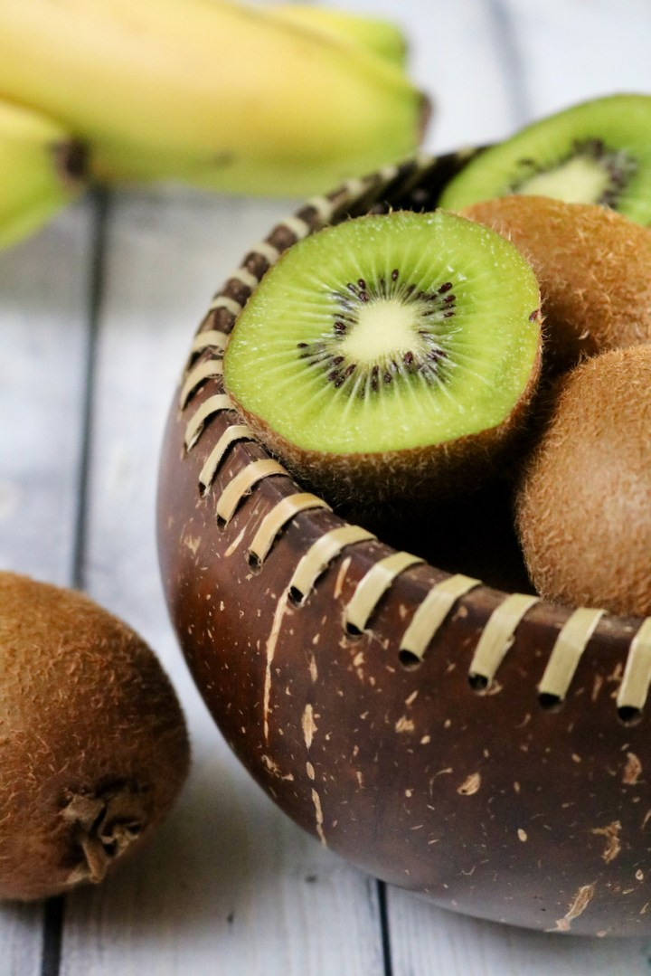 Fiber laced coconut shell bowl being used to hold kiwi with bananas in the background.