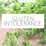 "The words ""gluten intolerance"" typed in front of a photo of herbs on a wood surface."