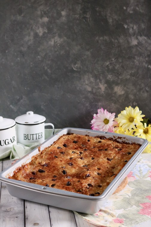 A 9x13 metal pan of gooey butter cake, pink and yellow flowers, and sugar and butter cups all in front of a gray background.