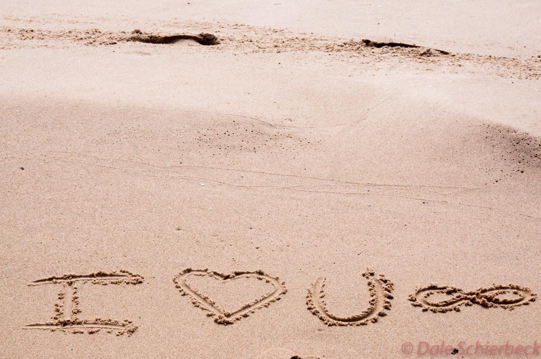 Love wishes written in sand