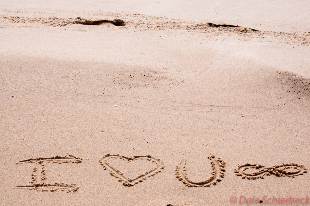 Love wishes written in sand