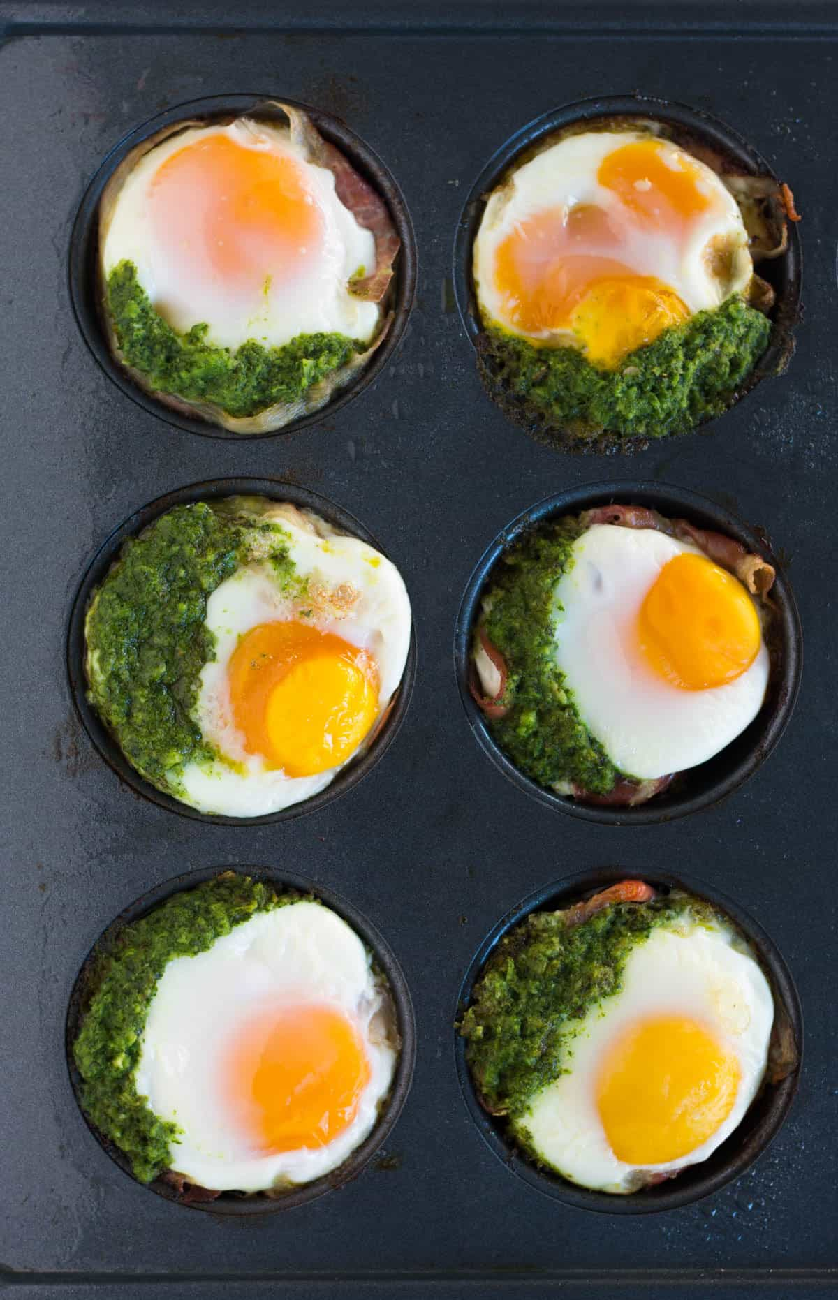 Overhead of 6 prosciutto egg cups with chimichurri in muffin tins