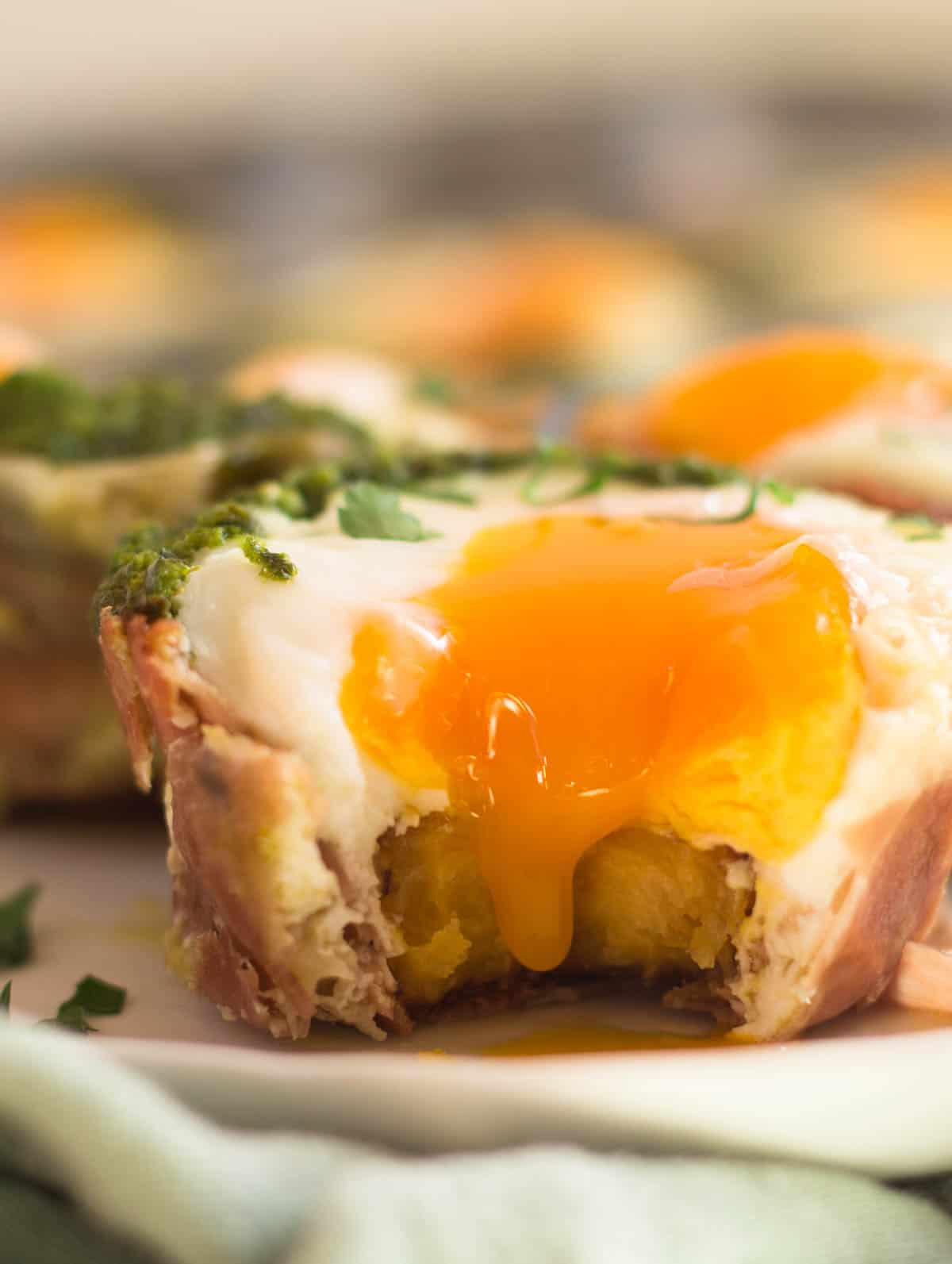 Close up of prosciutto egg cup with a bit taken out of it and the yolk running down