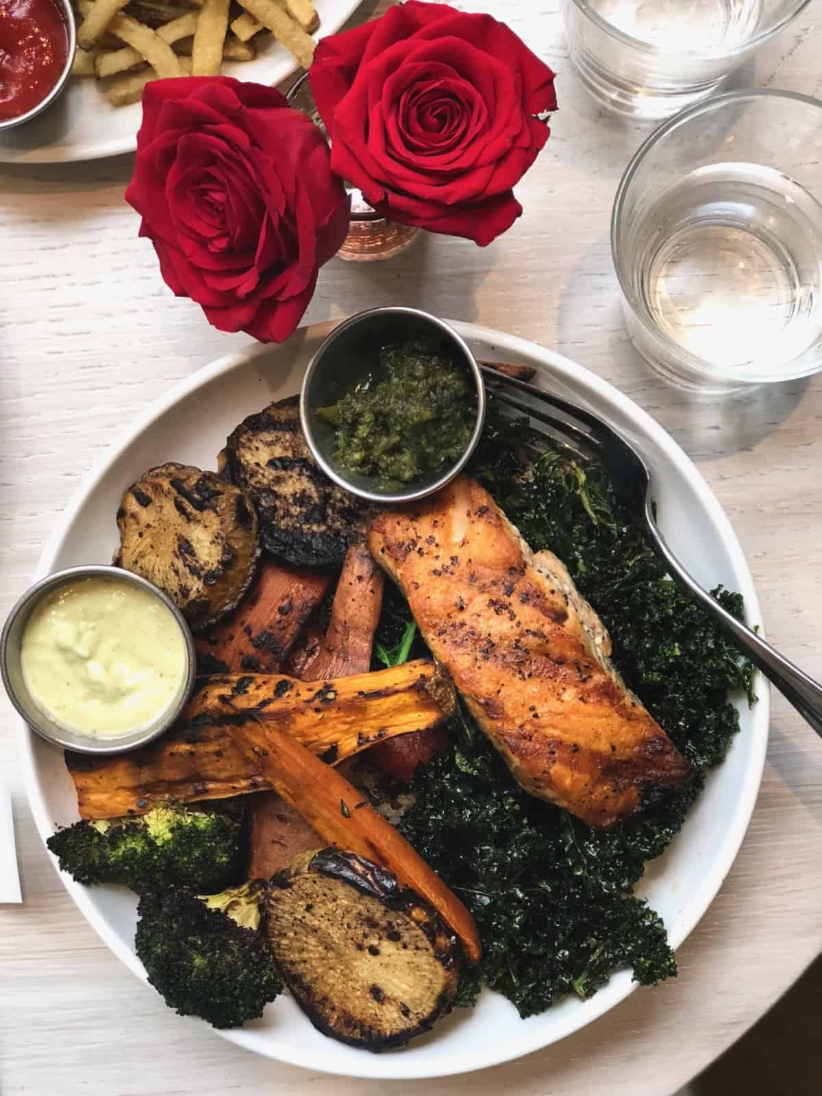 A table of a bowl of crispy kale, roasted veggies, and salmon with two sauces on the side, two red roses, and a glass of water