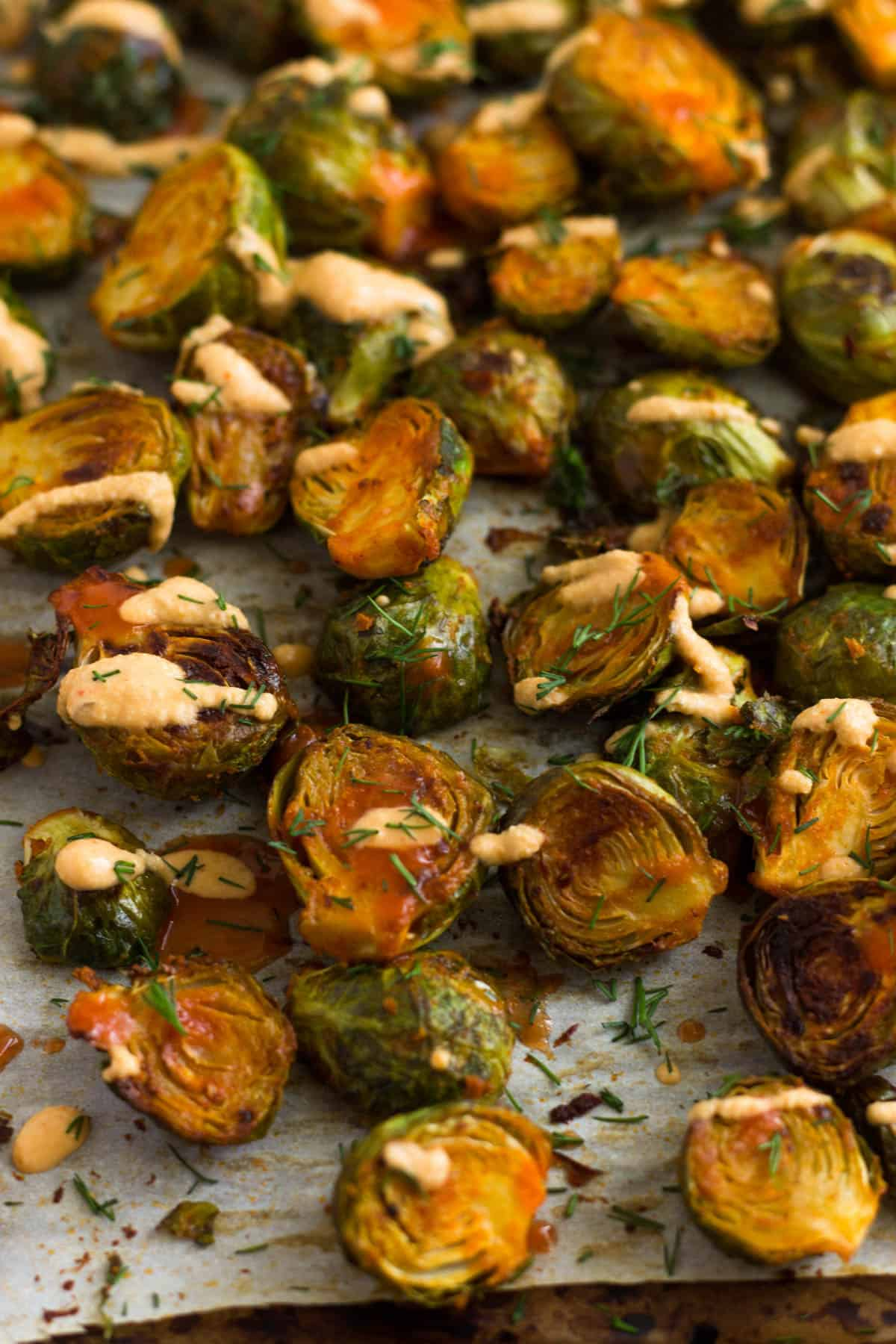 Pan of roasted buffalo brussel sprouts with fresh dill and vegan cheesy buffalo sauce