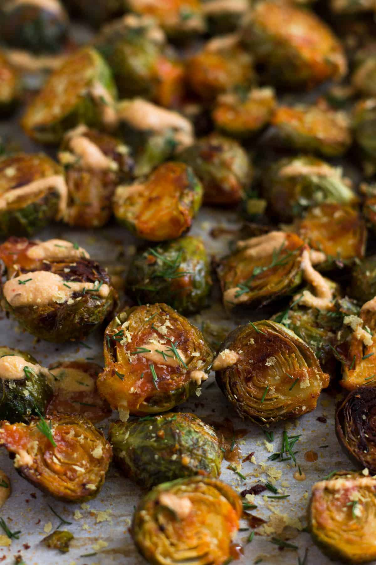Pan of roasted buffalo brussel sprouts topped with nutritional yeast, buffalo sauce, vegan cheesy buffalo sauce, and nutritional yeast.