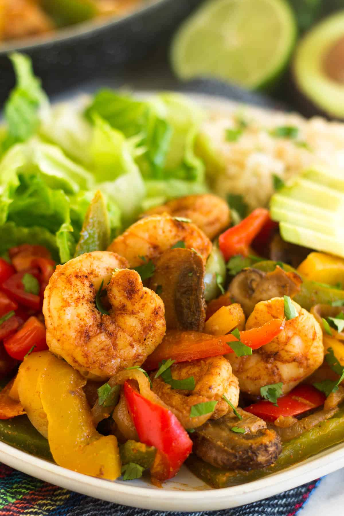 Close up of a plate with shrimp fajitas and sides