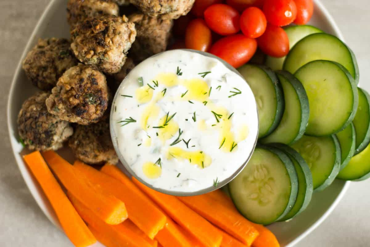 Overhead of a bowl of tzatziki sauce surrounded by fresh raw veggies and lamb meatballs