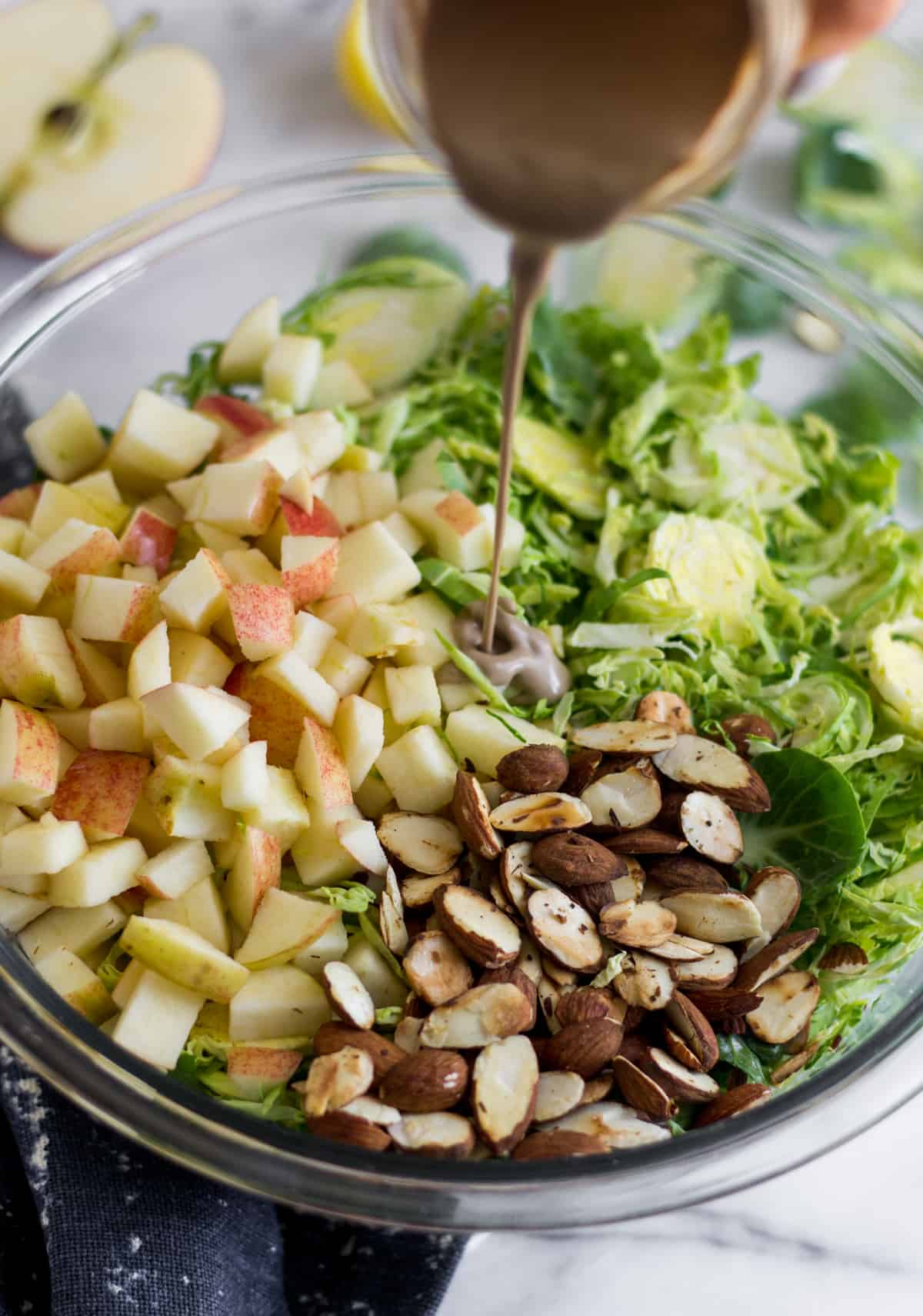 Glass bowl with shredded brussels sprouts, chopped apple, and toasted almonds and creamy balsamic dressing being poured into it