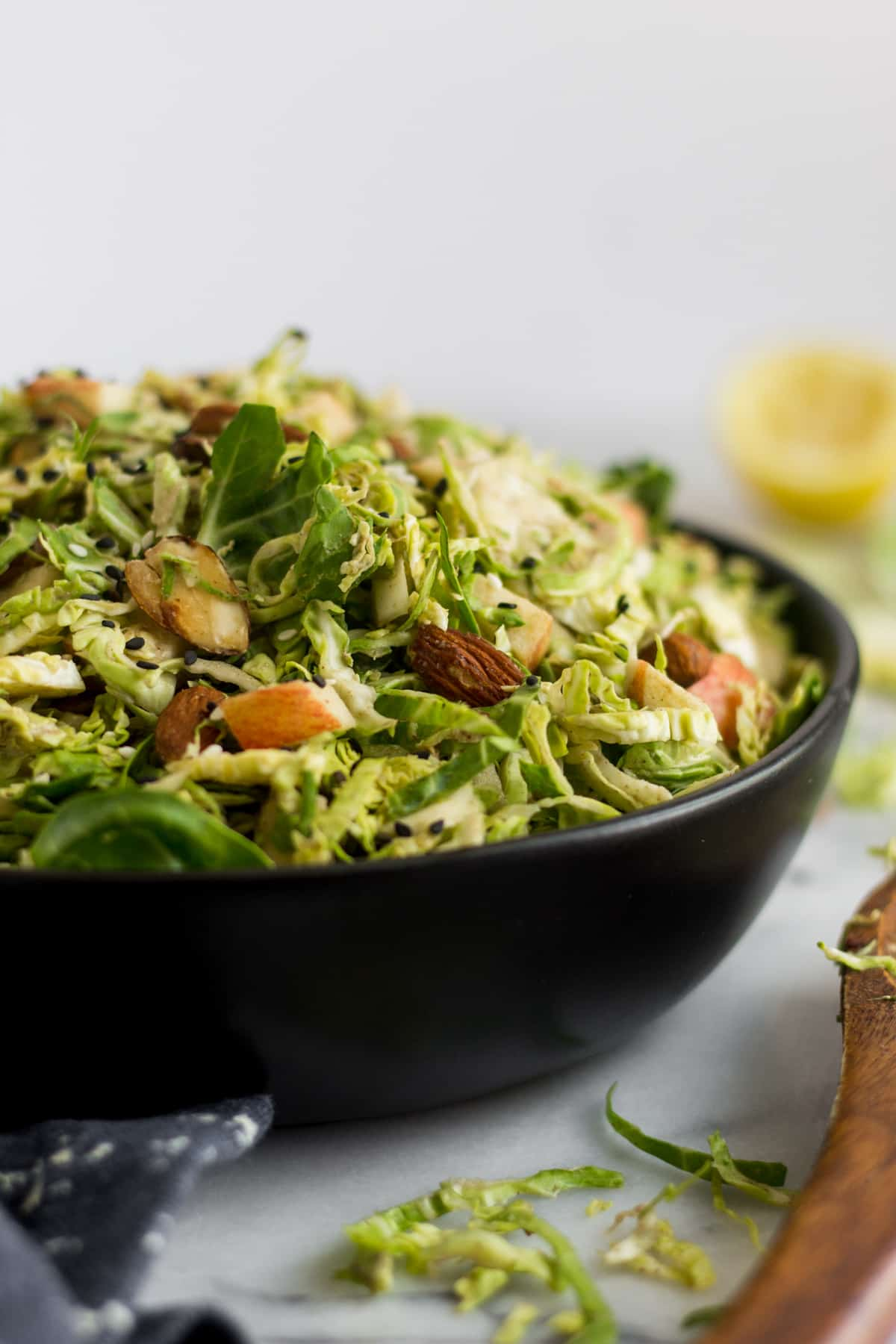 Straight on shot of a black bowl overflowing with apple & shaved brussels sprouts salad