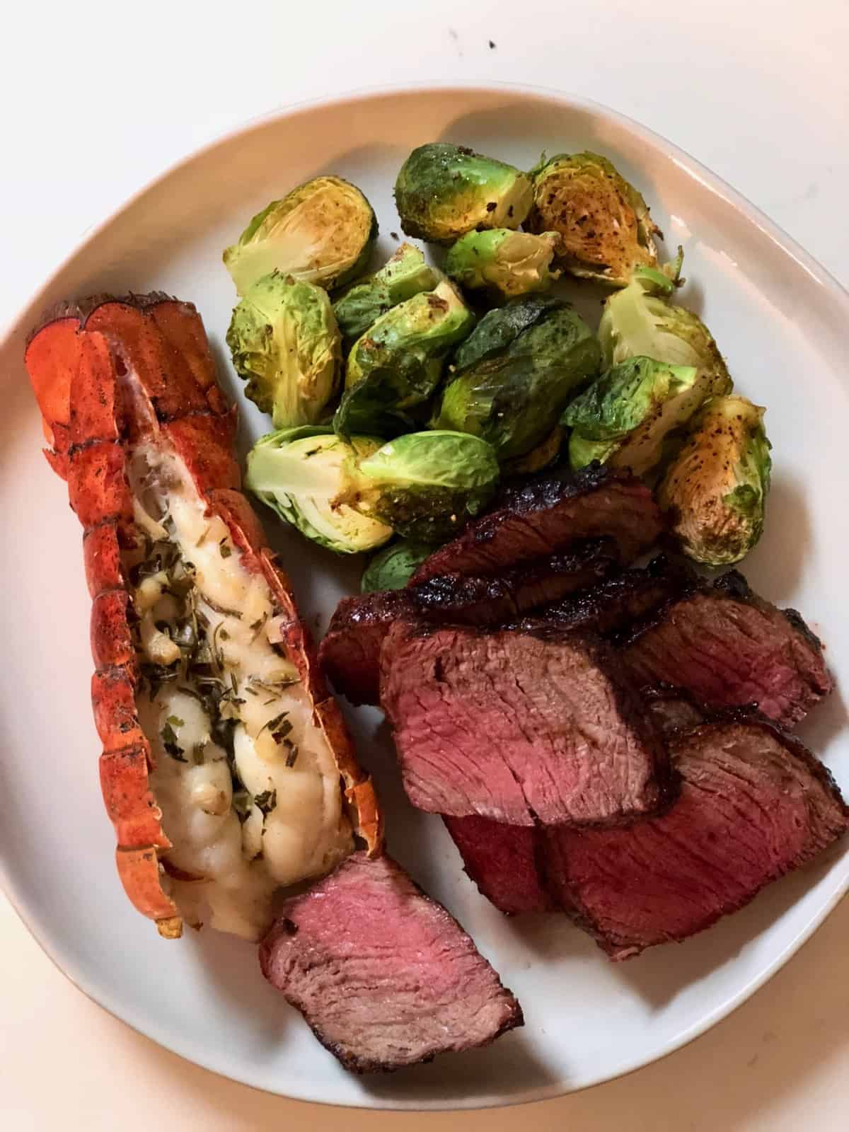 White plate of steak, brussel sprouts, and lobster