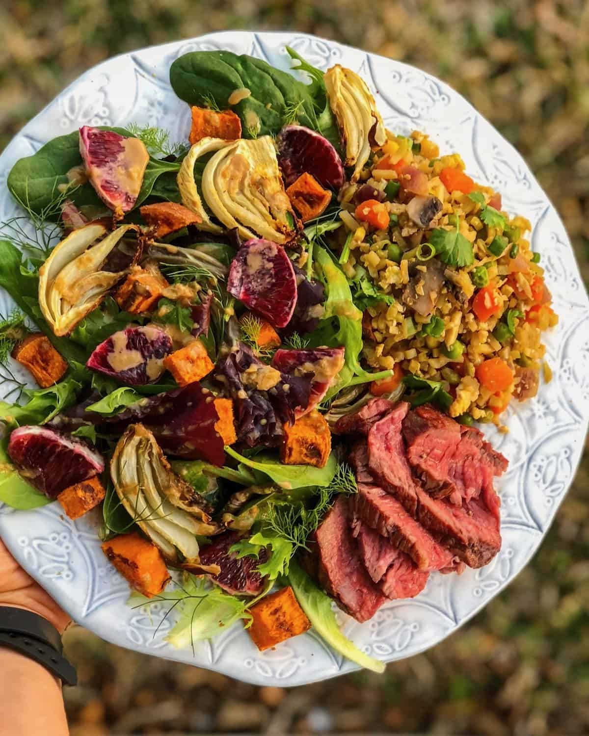Plate of a big salad with greens, roasted fennel, blood oranges, and sweet potatoes, steak, and broccoli fried rice