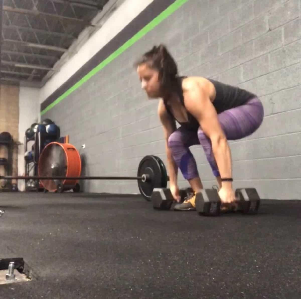 Girl squatting holding two dumbbells on the floor