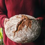 woman holding rustic loaf of no knead bread