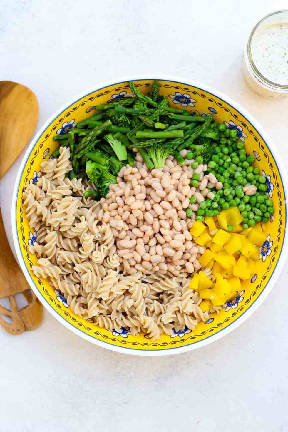 All of the ingredients for the pasta salad in a bowl getting ready to be mixed up.