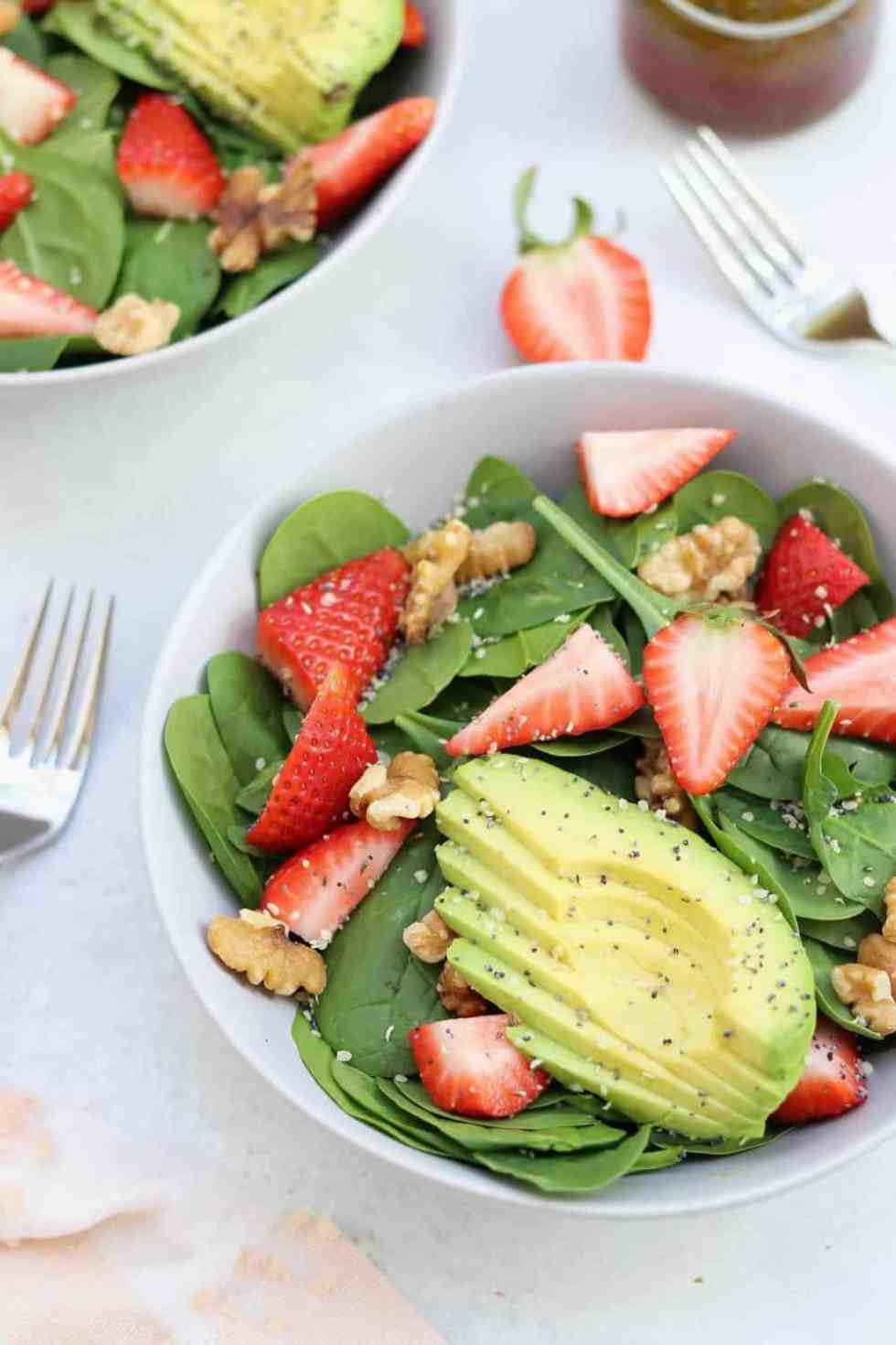 strawberry spinach salad with avocado in a grey bowl with two forks.