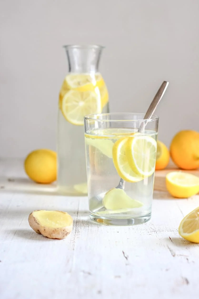 Lemon and ginger water in a glass cup with metal spoon on a white backdrop.